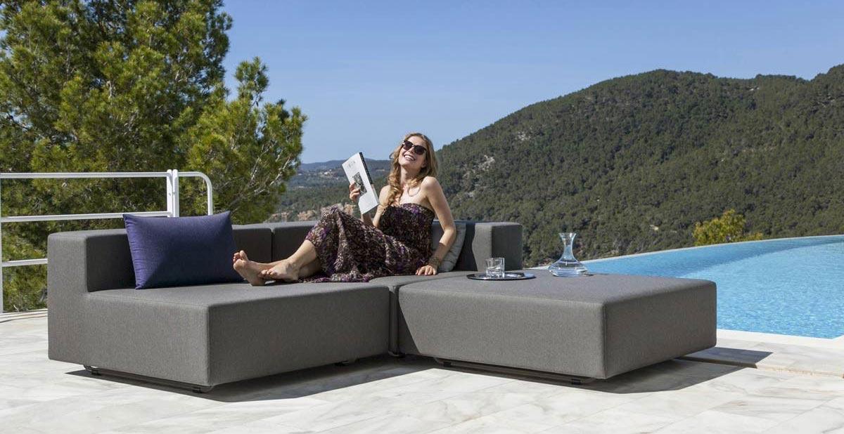 Frau sitzt auf dem Balkon auf Outdoor Lounge Sofa